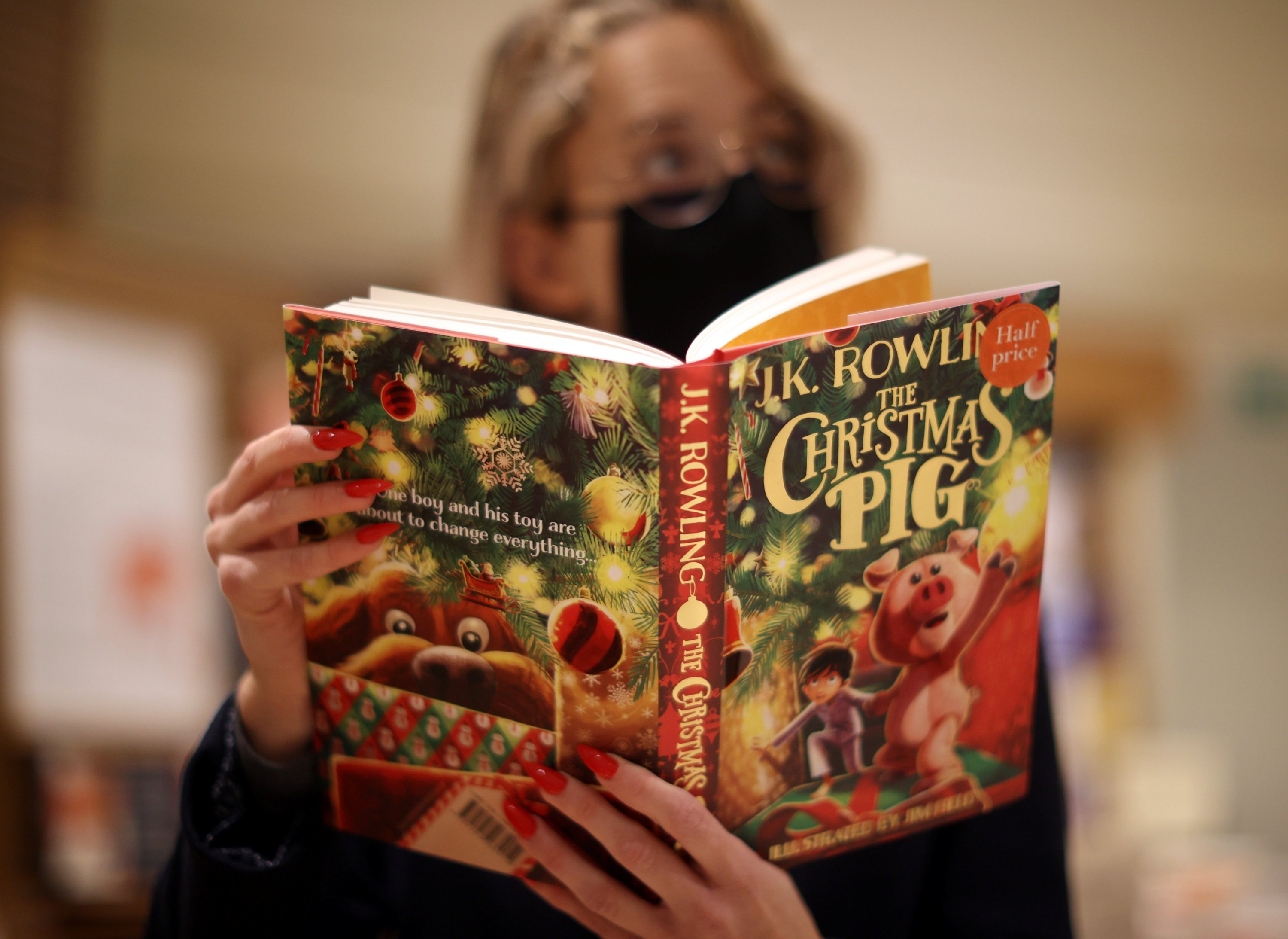 A shop worker poses with a copy of 'The Christmas Pig,' a children's book written by J. K. Rowling, at a Waterstones store in London, England, Oct. 12, 2021. (REUTERS Photo)