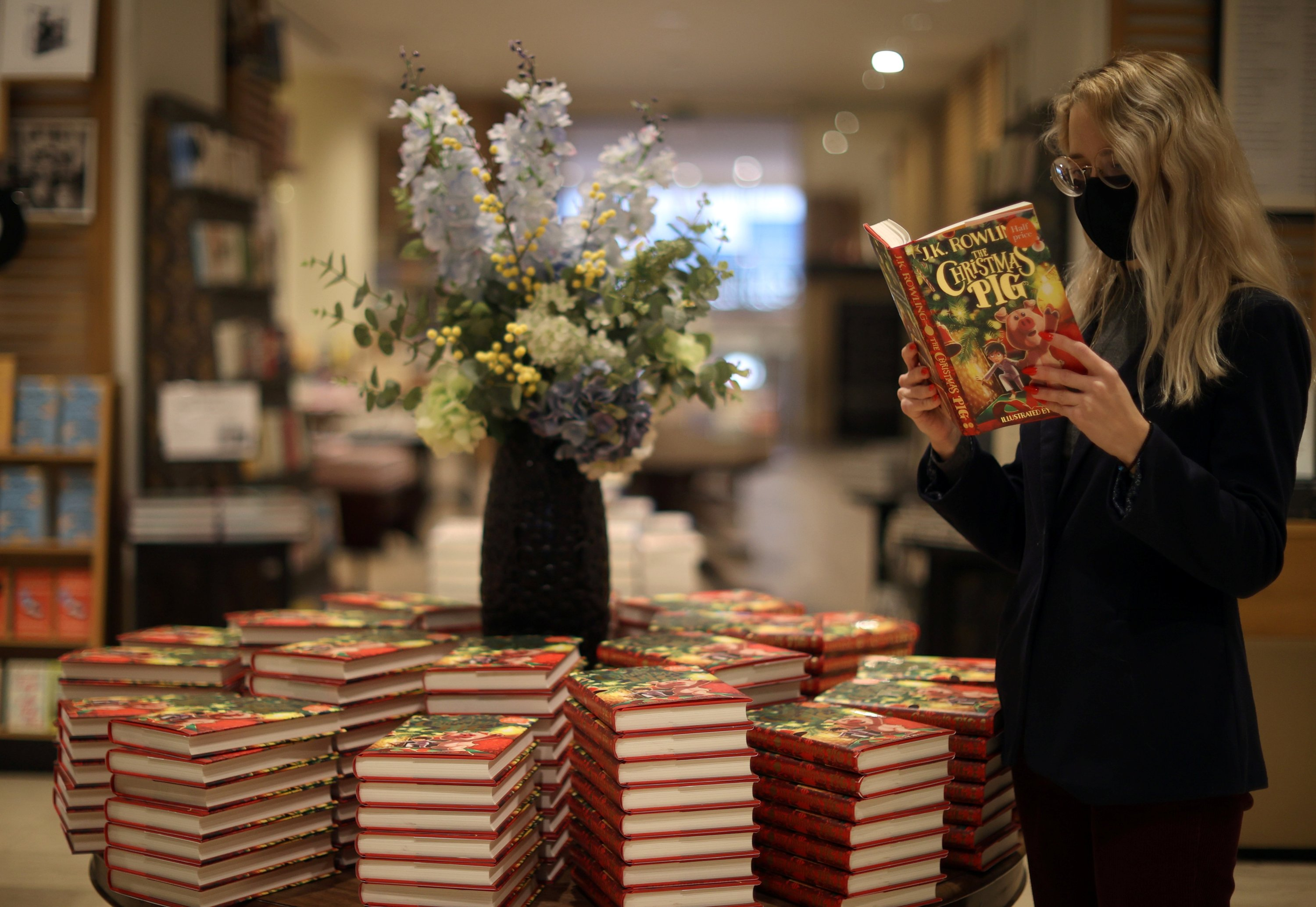 A shop worker poses with a copy of 'The Christmas Pig', a children's book written by J. K. Rowling, at a Waterstones store in London, England, Oct. 12, 2021. (REUTERS Photo)