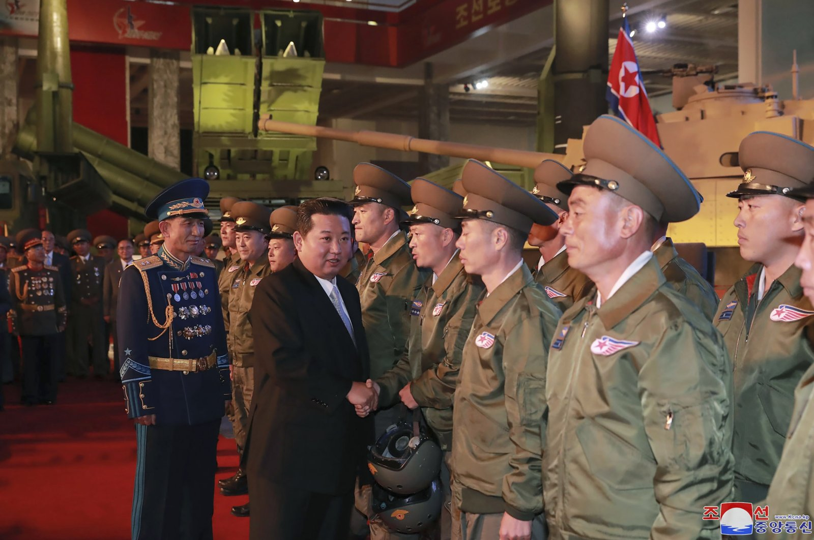 In this photo provided by the North Korean government, North Korean leader Kim Jong Un (2nd L) meets fighter pilots who made the demonstration flight at the opening of an exhibition of weapons systems in Pyongyang, North Korea, Oct. 11, 2021. (Korean Central News Agency/Korea News Service via AP)