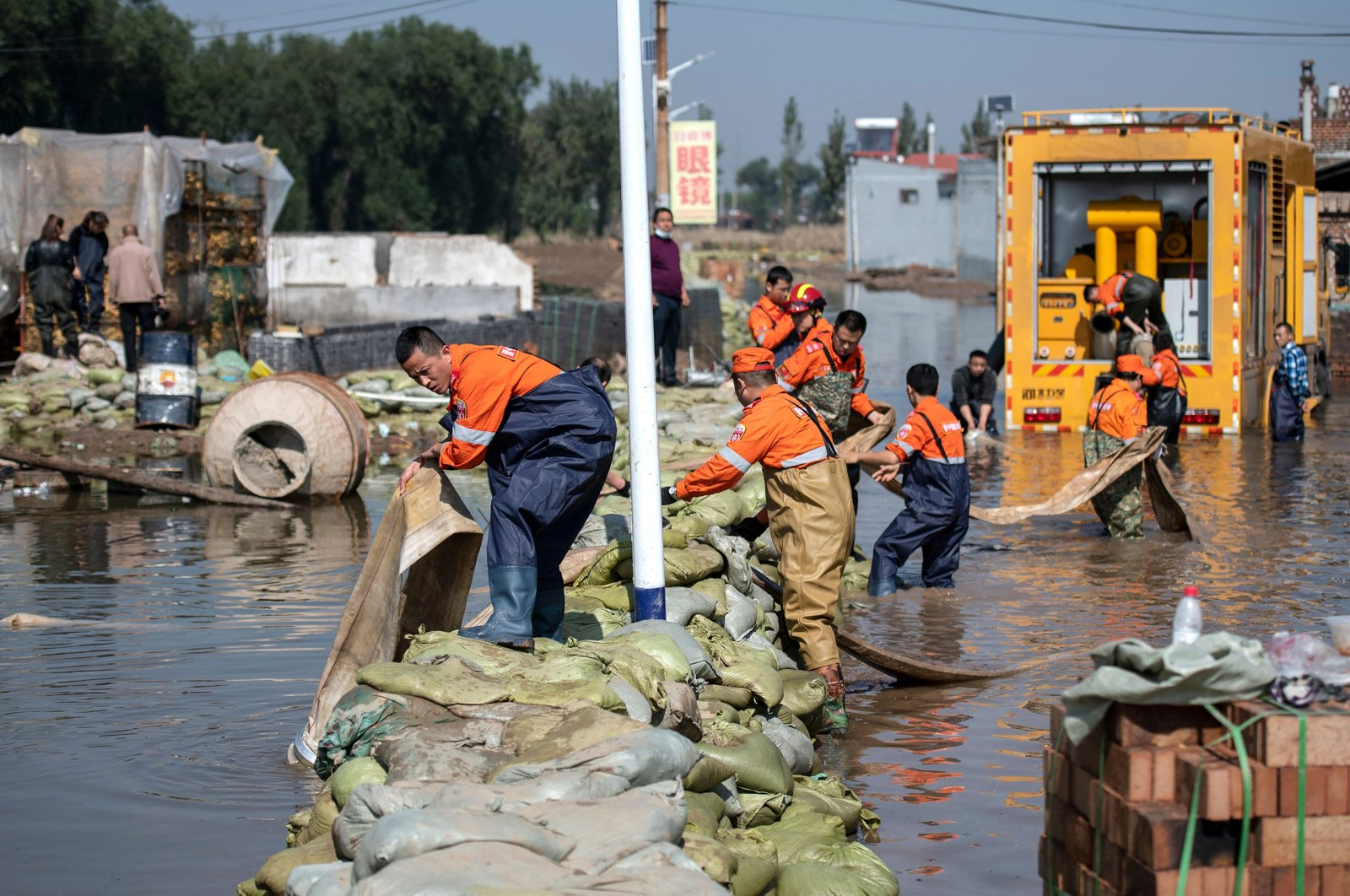Rescue workers drain off flood waters after heavy rainfall at a flooded area in Jiexiu in the city of Jinzhong in China's northern Shanxi province on Oct. 11, 2021. (AFP Photo)