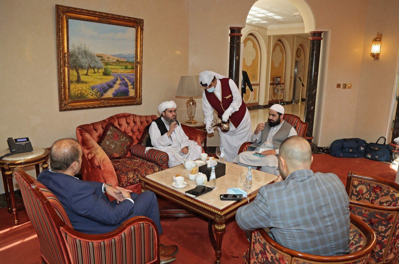 Taliban's former envoy to Saudi Arabia Shahabuddin Delawar (C) sips coffee before a meeting with foreign diplomats in Qatar's capital Doha, Oct. 12, 2021. (AFP Photo)