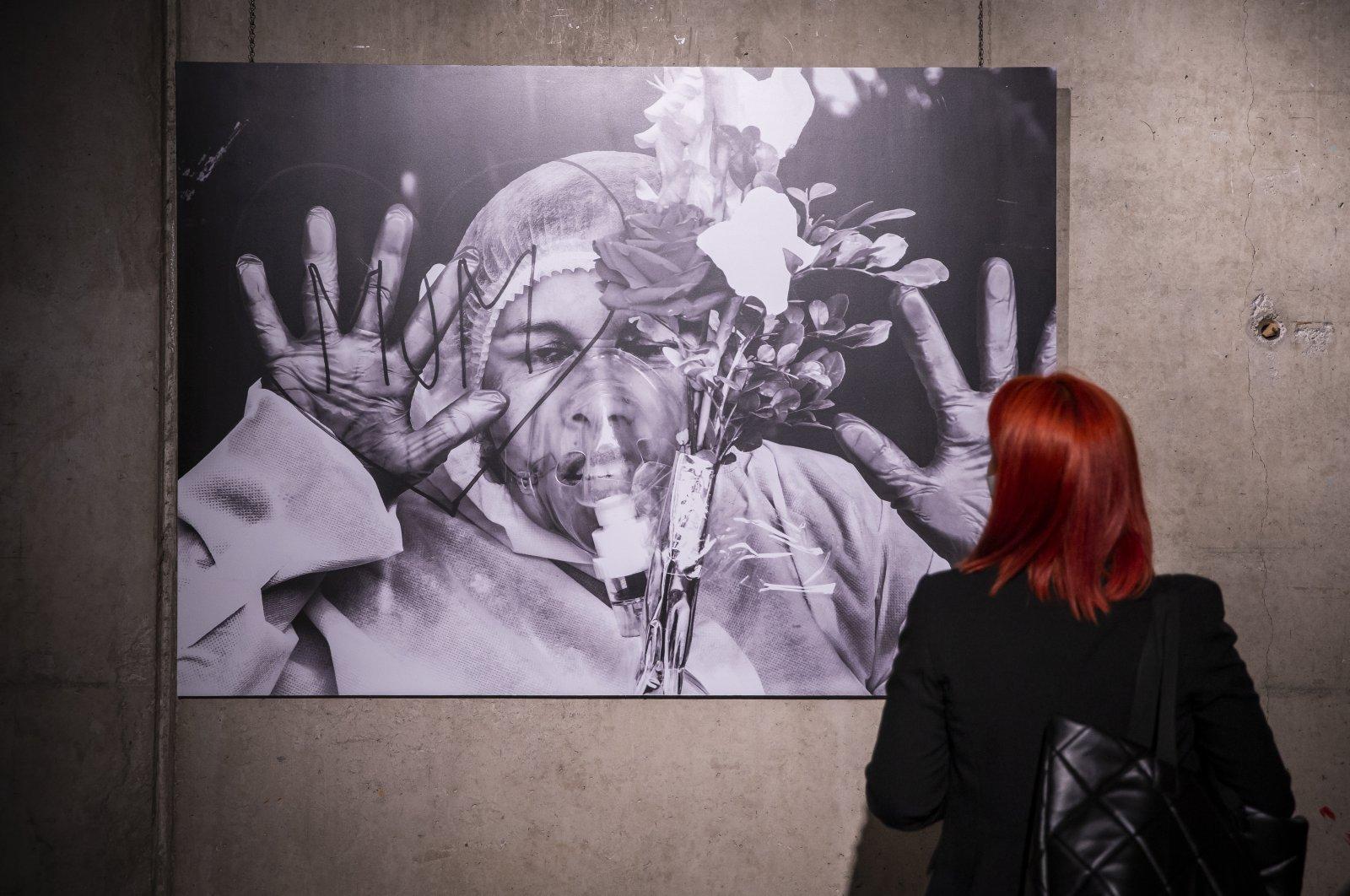 """A visitor examines Mohammed Shajahan's photo titled """"Mom Love,"""" winner of the Photo of the Year Award, CerModern Arts Center, Ankara, Turkey, Oct. 11, 2021. (AA Photo)"""