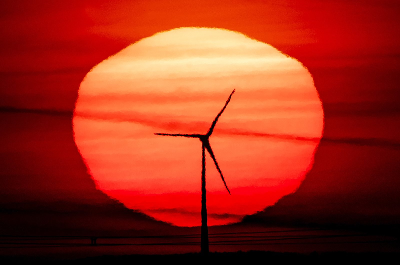 The sun rises behind a wind turbine in Frankfurt, Germany, Sept. 15, 2020. (AP Photo)