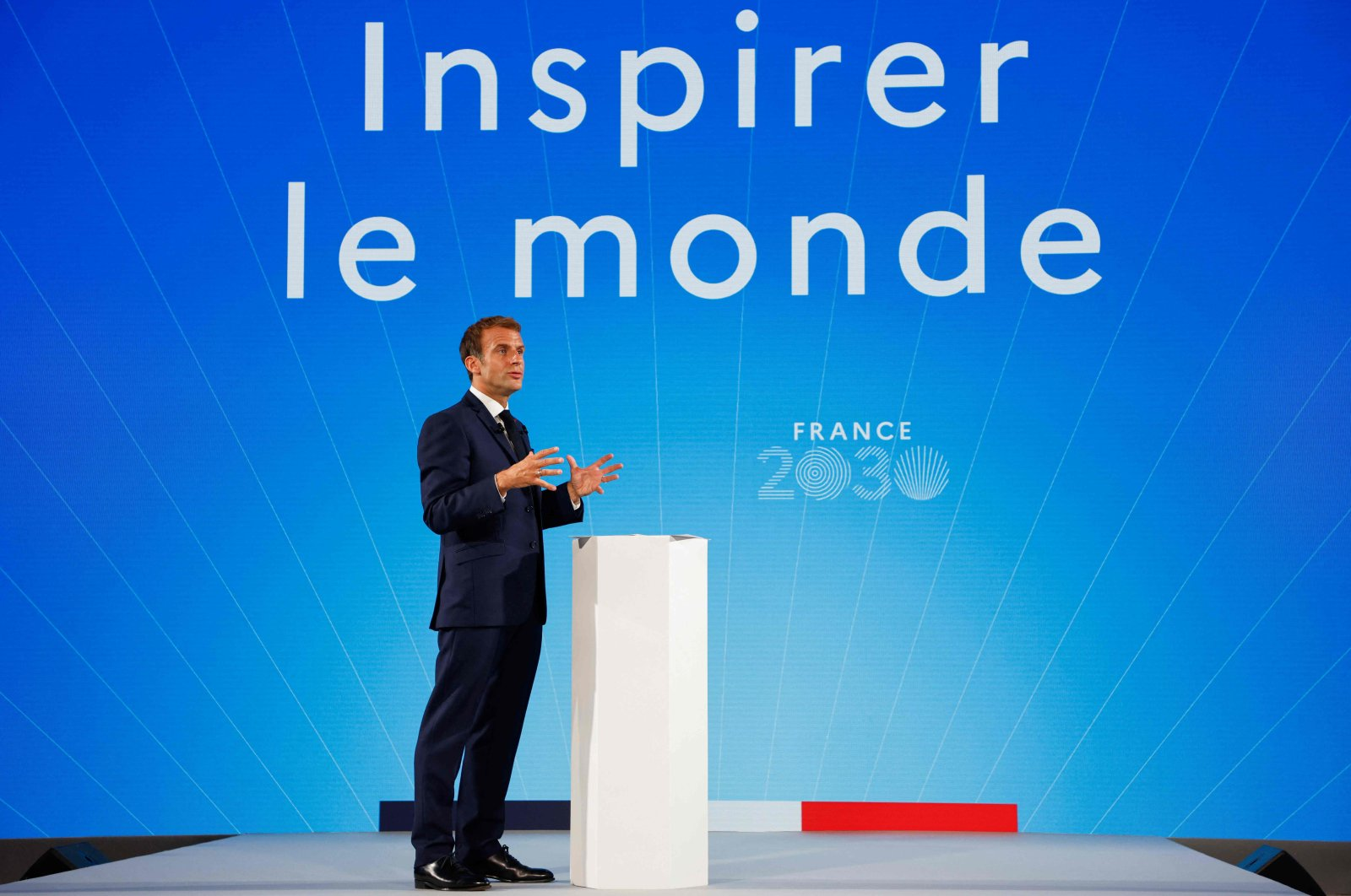 """French President Emmanuel Macron gestures as he speaks in front of a screen with the words reading """"Inspire the world"""" during the presentation of the """"France 2030"""" investment plan at The Elysee Presidential Palace in Paris, France, Oct. 12, 2021. (AFP Photo)"""