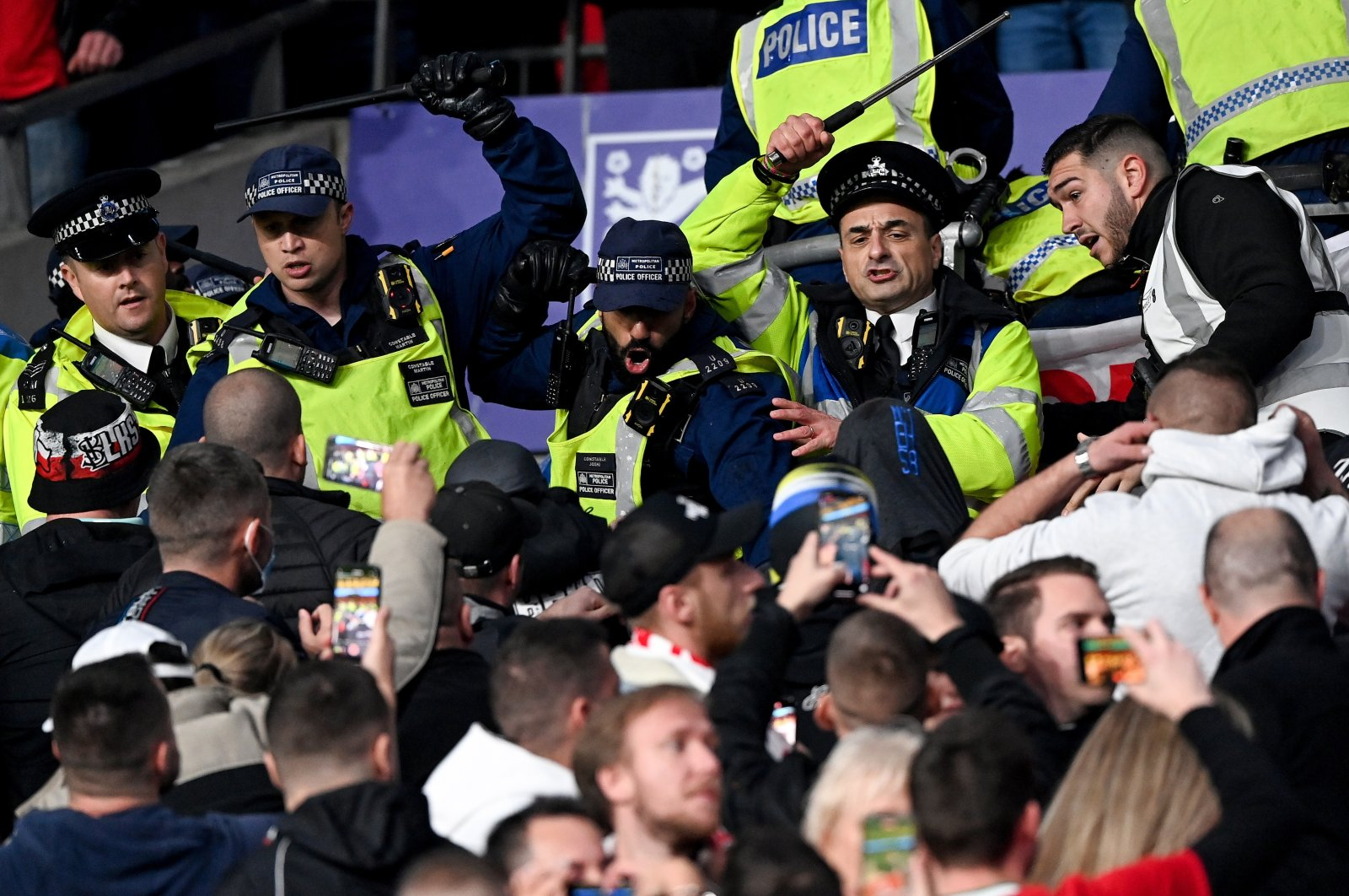 Police officers in the stands use batons against Hungarian fans during the FIFA World Cup Qatar 2022 qualifying Group I soccer match between England and Hungary at Wembley-Stadium in London, Britain, Oct. 12, 2021. (EPA Photo)