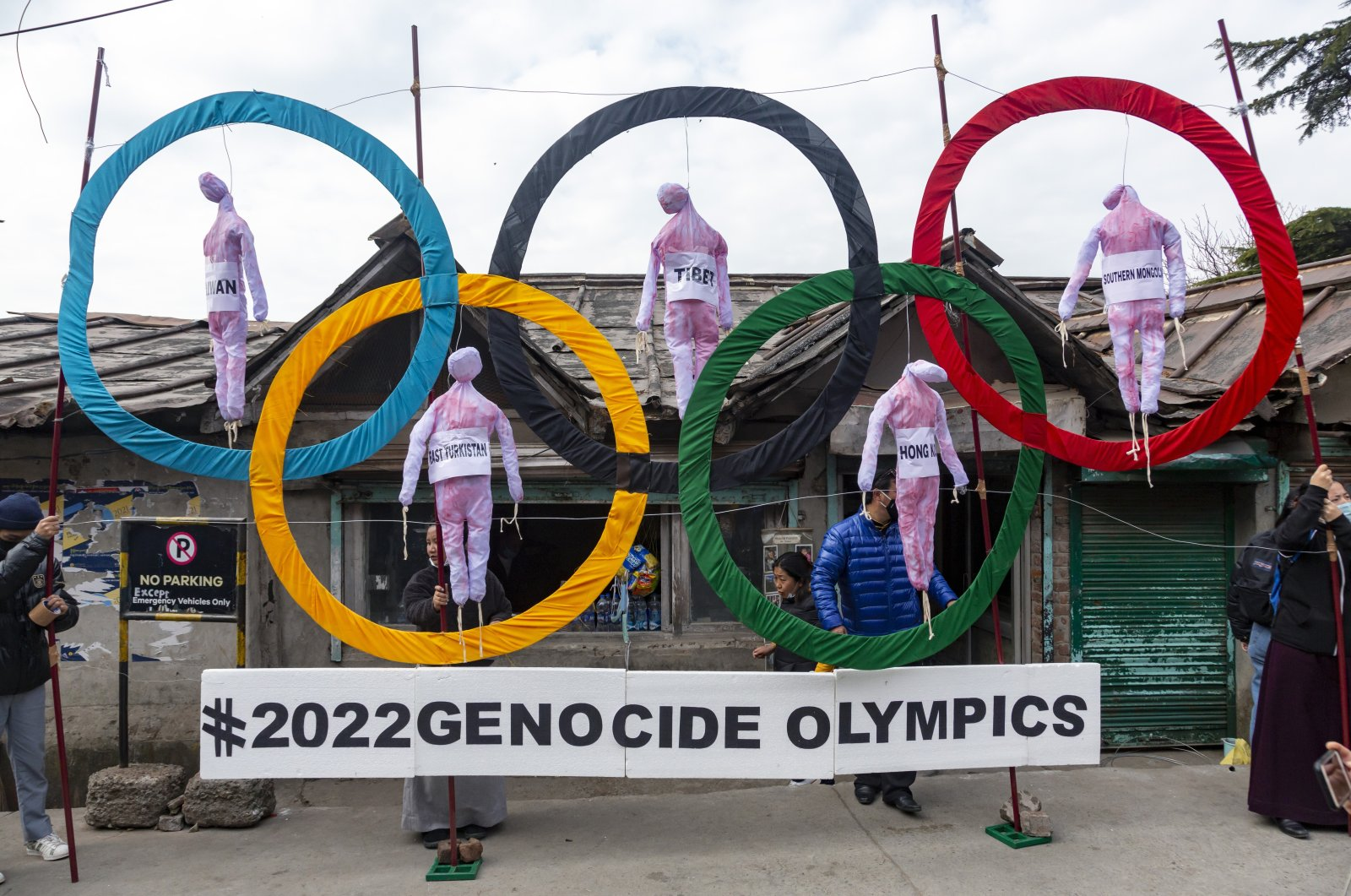 Exiled Tibetans use the Olympic Rings as a prop as they hold a street protest against the holding of 2022 Winter Olympics in Beijing, in Dharmsala, India, Feb. 3, 2021. (AP Photo)