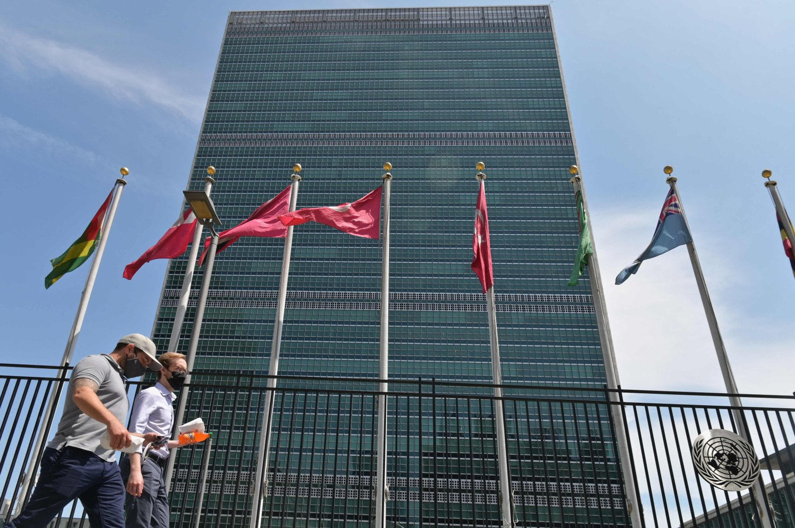 People walk past flags outside the United Nations headquarters in New York City, U.S., May 20, 2021. (AFP Photo)