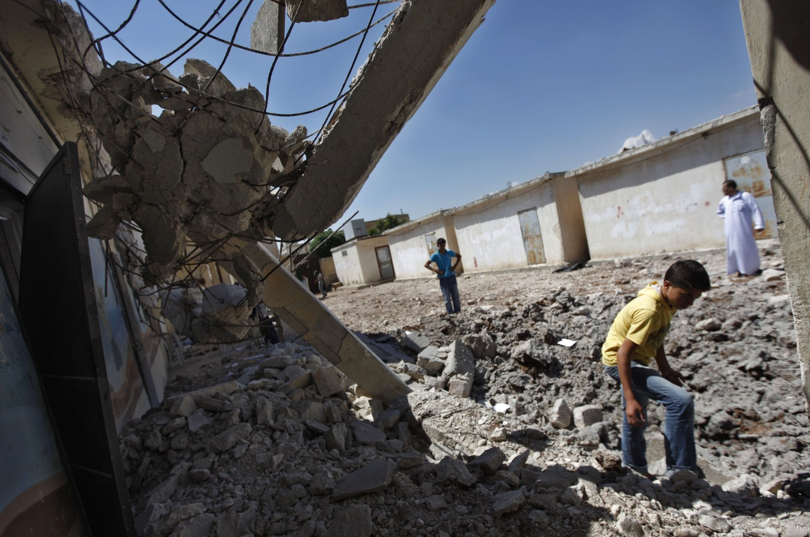 Syrians check the damage at a destroyed school after it was hit by an airstrike killing six Syrians in town of Tal Rifaat on the outskirts of Aleppo, Syria, Aug. 8, 2012. (AP File Photo)