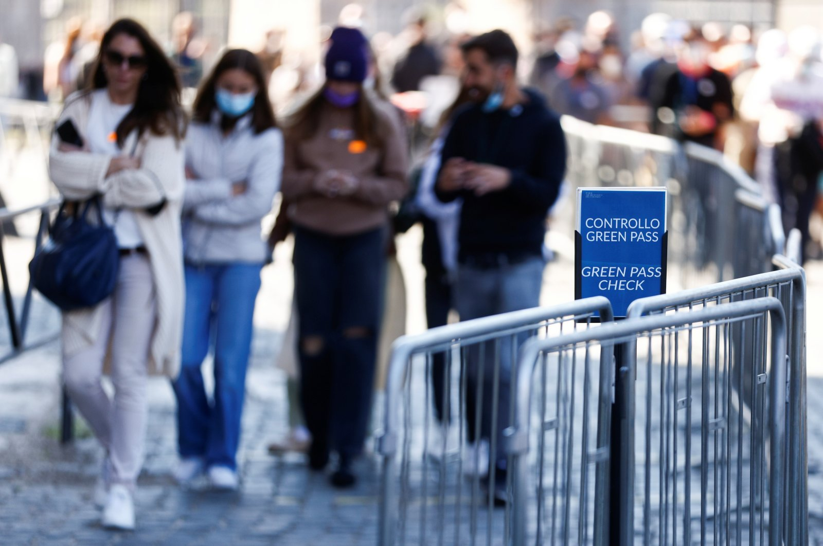 """People walk past a sign reading """"Green Pass check"""" as they enter the Colosseum as Italy prepares to become the first European country to make the COVID-19 """"Green Pass"""" mandatory for all workers, Rome, Italy, Oct. 13, 2021. (Reuters Photo)"""