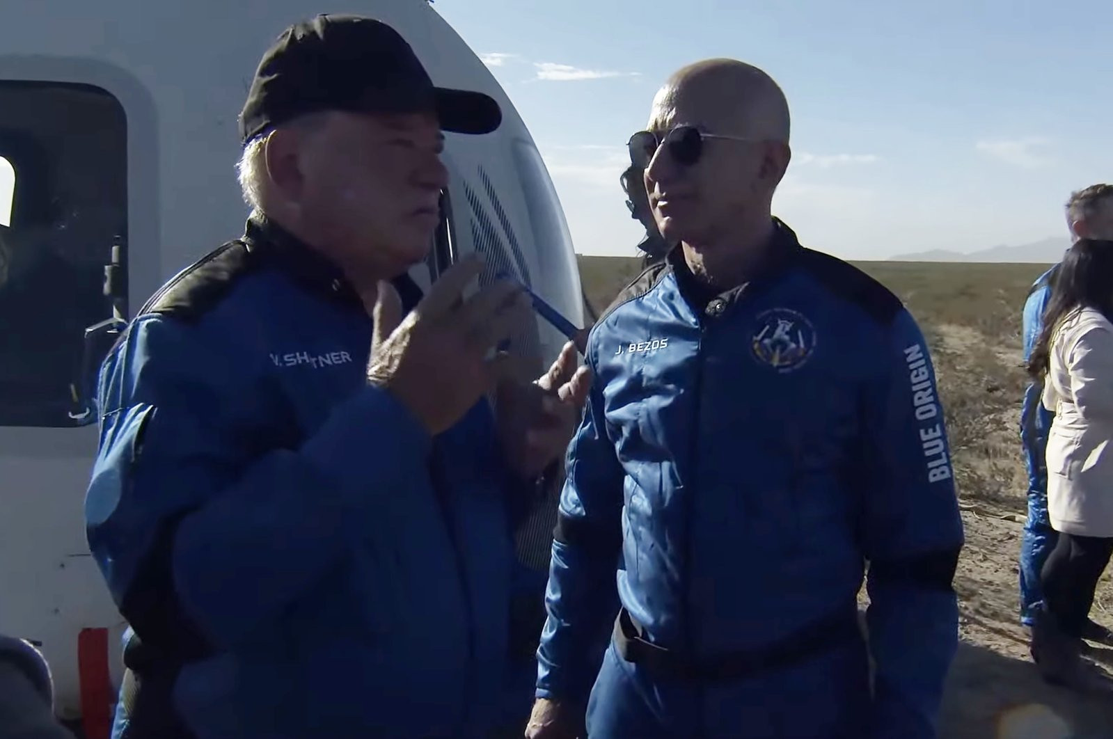 A handout screengrab released by Blue Origin shows Jeff Bezos (R) greeting Canadian actor William Shatner (L) as he emerges from the capsule after landing following the New Shepard's NS-18 mission to space near Van Horn, Texas, U.S., Oct. 13, 2021. (Blue Origin Handout/EPA)