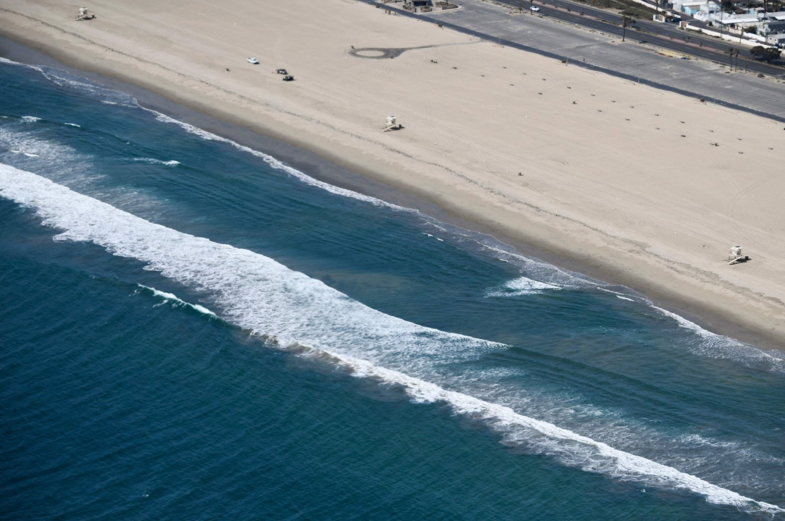 Closed lifeguard towers and mostly empty coastline are seen from a U.S. Coast Guard HC-27J Spartan aircraft during a media flight after an oil spill in the Pacific Ocean in Orange County, California, U.S., Oct. 6, 2021. (AFP Photo)