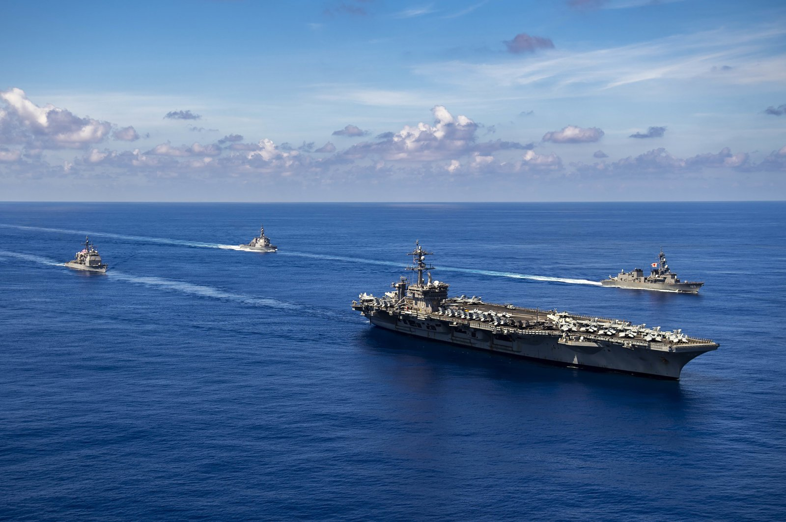 In this photo released by the U.S. Navy, the Nimitz-class aircraft carrier USS Carl Vinson (CVN 70), the Ticonderoga-class guided-missile cruiser USS Lake Champlain (CG 57), and the Arleigh Burke-class guided-missile destroyer USS Chafee (DDG 90) conduct a passing honors ceremony with the Japan Maritime Self-Defense Force (JMSDF) Murasame-class destroyer JS Ikazuchi (DD 107) and the Kongo-class guided-missile destroyer JS Chokai (DDG 176) in the Pacific Ocean, Sept. 19, 2021. (AP Photo)