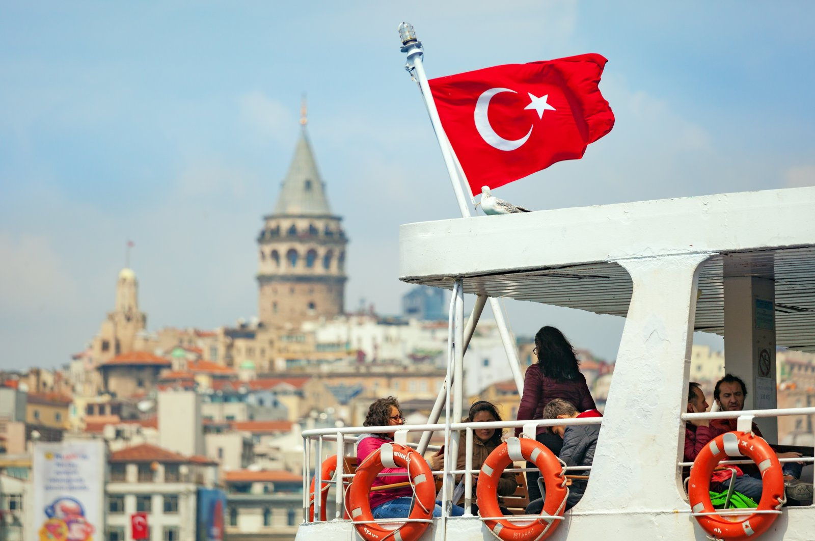 Tourists travel by ferry across the Golden Horn inlet with the famous Galata Tower in the background, Istanbul, Turkey, April 23, 2017. (Shutterstock Photo)