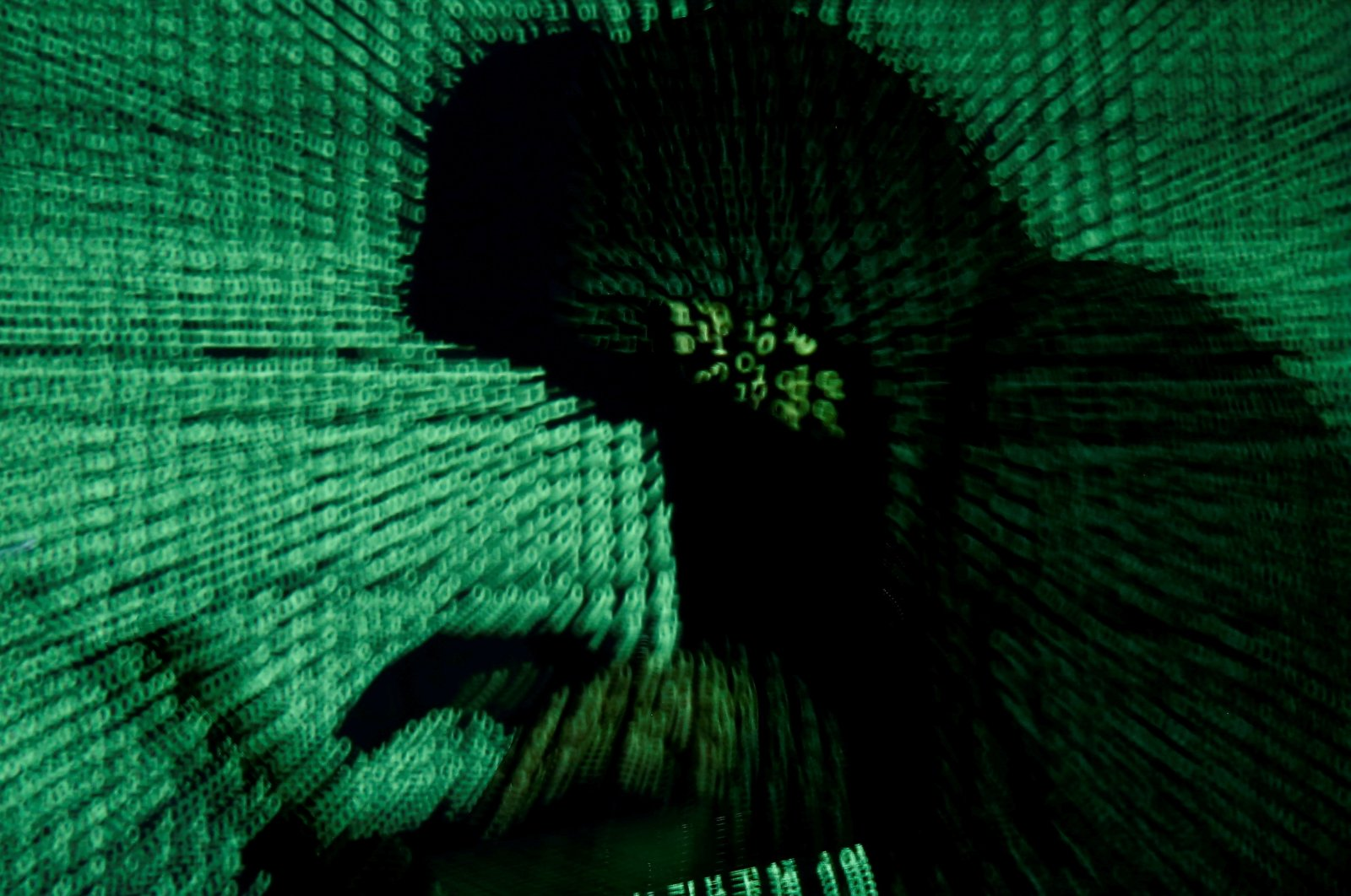 A man holds a laptop computer as cyber code is projected on him in this illustration picture taken on May 13, 2017. (Reuters Photo)