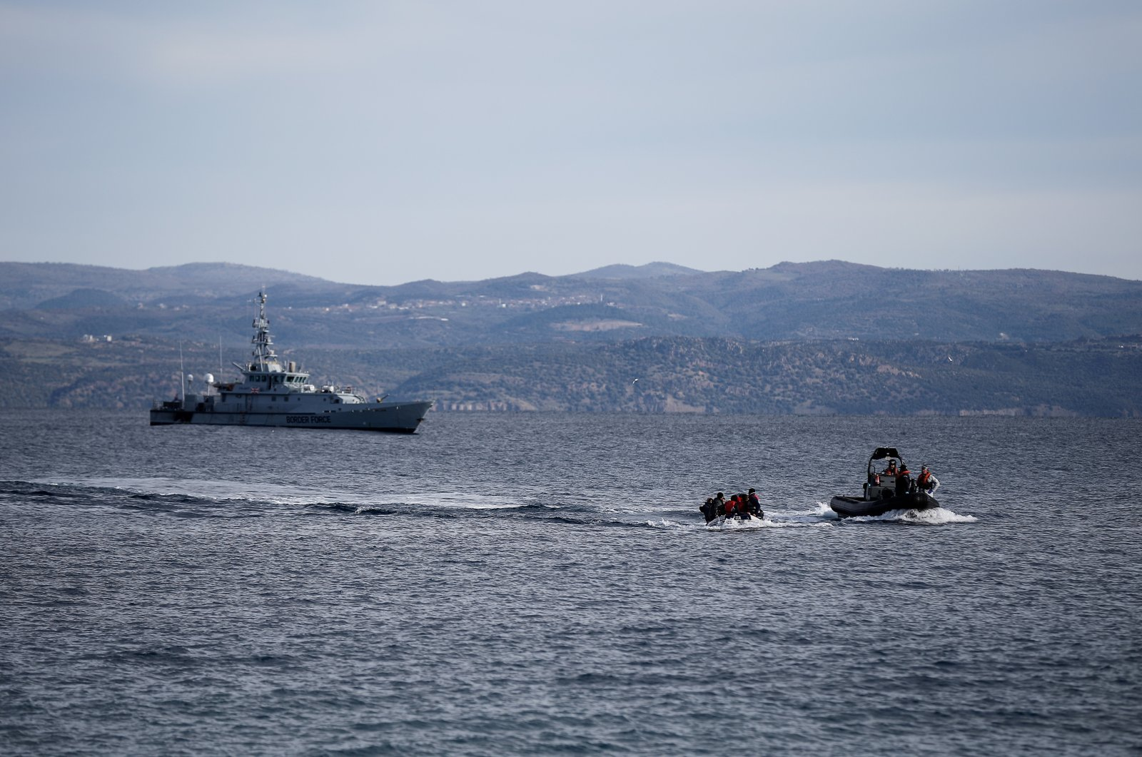 A rescue boat escorts a dinghy with migrants from Afghanistan as a Frontex vessel patrols in the background, on the island of Lesbos, Greece, Feb. 28, 2020. (Reuters File Photo)