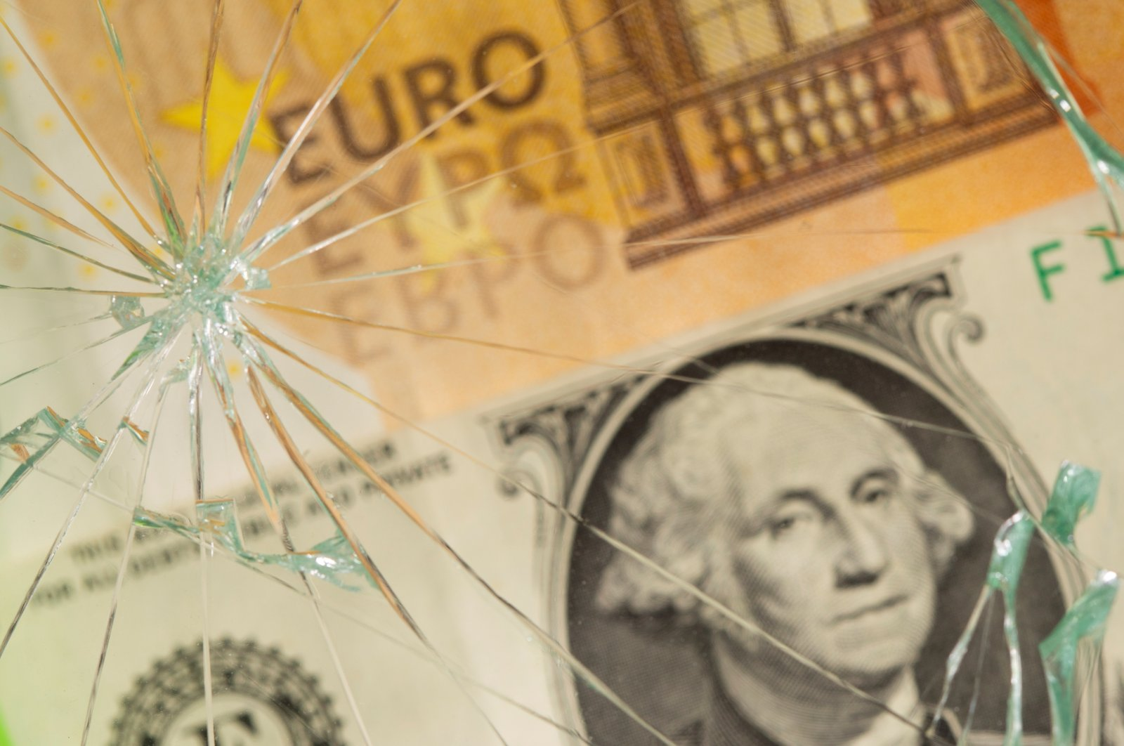 U.S. dollar and euro banknotes are seen through broken glass in this illustration taken, June 25, 2021. (Reuters Photo)