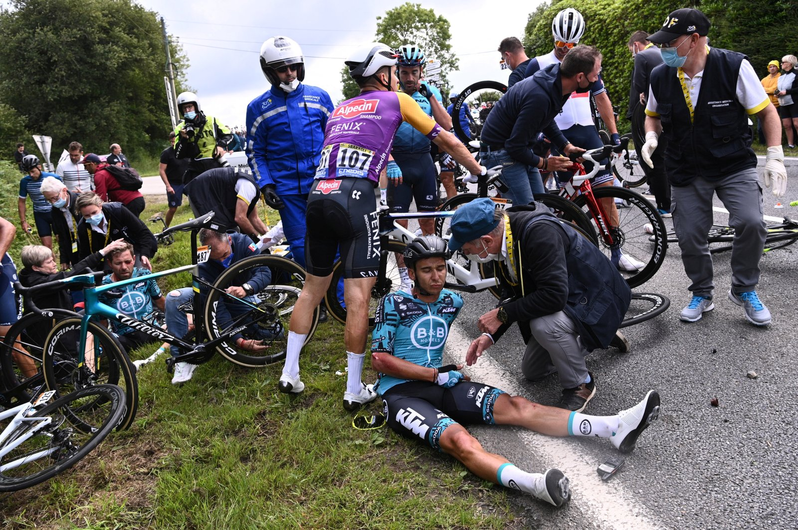 Cyclist Cyril Lemoine of France receives medical attention after crashing during the first stage of the Tour de France that stretches over 197.8 kilometers (122.9 miles) with a start in Brest and finish in Landerneau, France, June 26, 2021.