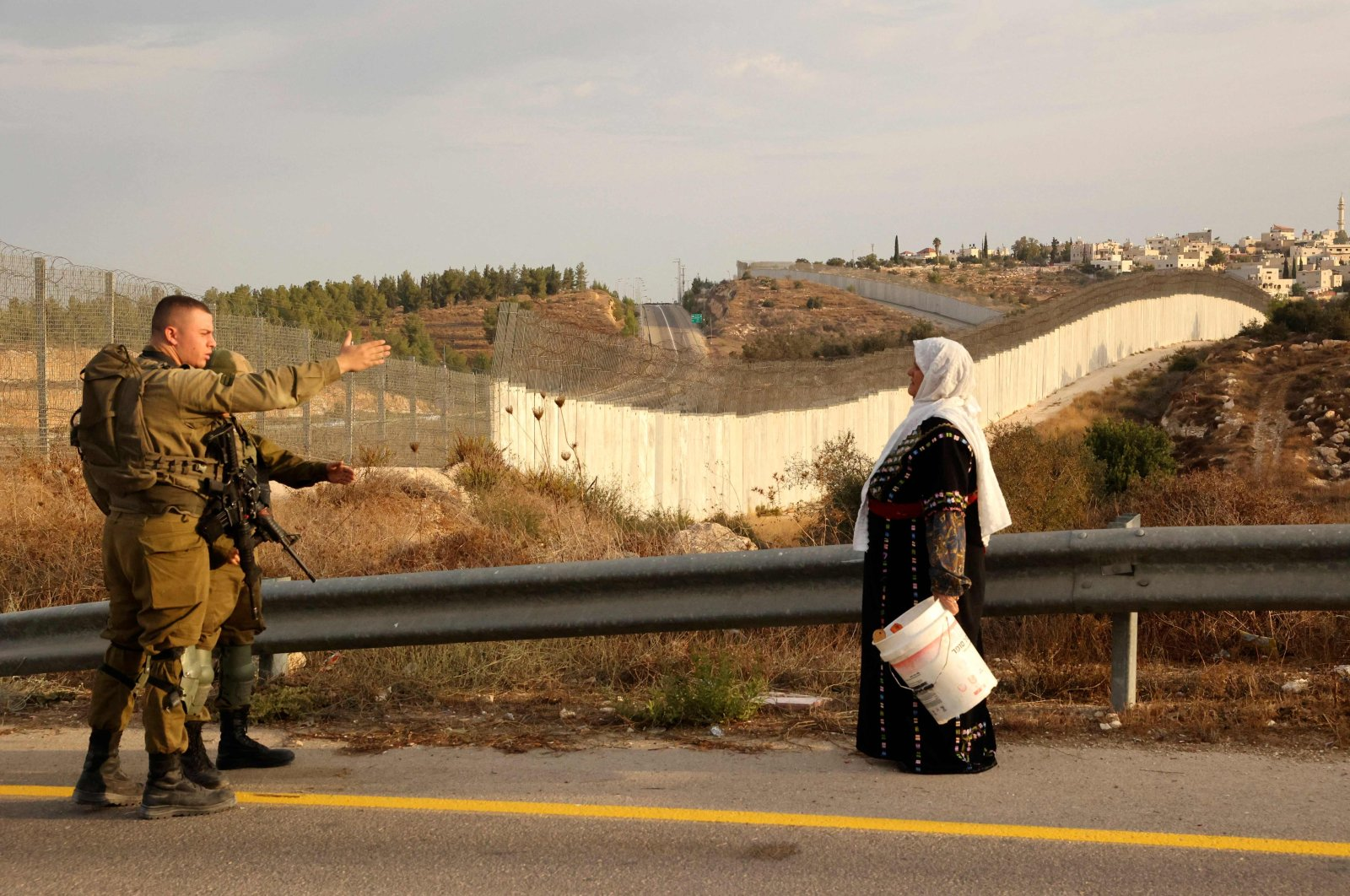 A Palestinian woman stands with others (not pictured) as they gather near an Israeli army checkpoint and wait to reach their olive fields on the other side of Israel's separation barrier (background), near the village of Bait A'wa on the outskirts of the West Bank city of Hebron, occupied Palestine, Oct. 13, 2021. (AFP Photo)