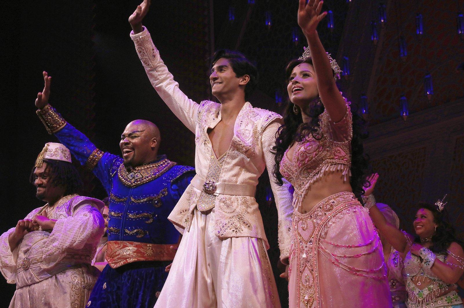 "Michael James Scott (C-L) as Genie, Michael Maliakel (C) as Aladdin, and Shoba Narayan (R) as Jasmine after a performance of the Broadway musical ""Aladdin"" in New York, U.S., Sept. 28, 2021. (Disney Theatrical Productions via AP)"