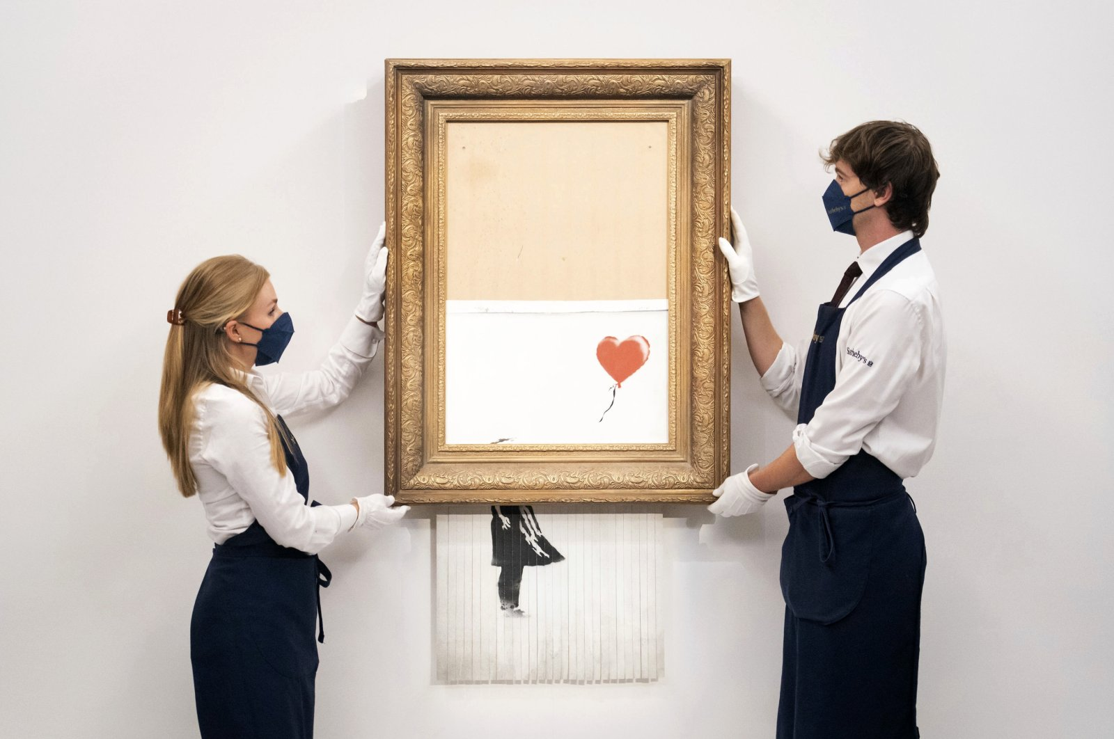 """Art handlers at Sotheby's auction house hold Banksy's """"Love is in the Bin,"""" before it returns to auction at Sotheby's, London, U.K., Sept. 3, 2021. (AP Photo)"""