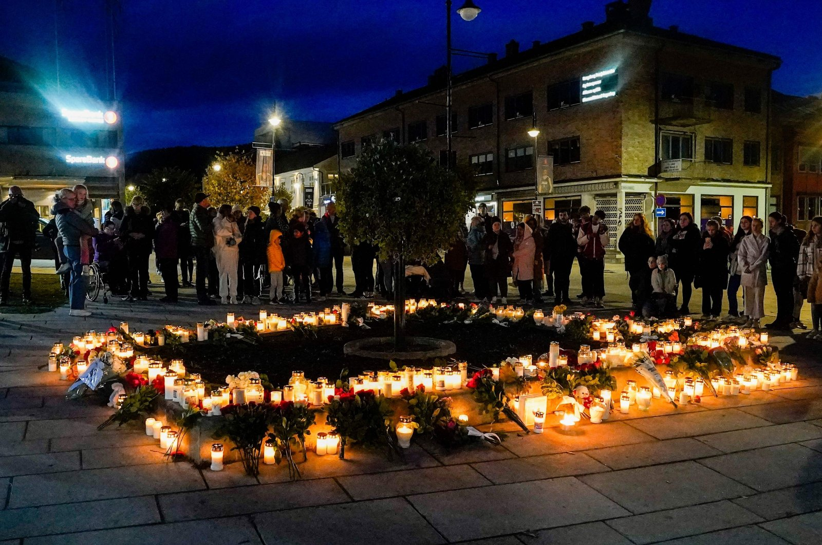 People lay flowers and light candles on the Stortorvet to honor the victims of the terrorist attack in Kongsberg, Norway, Oct. 14, 2021. (AFP Photo)